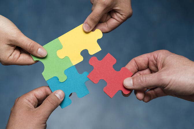 Hands holding pieces of a puzzle